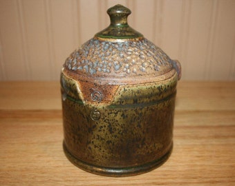 Handmade pottery covered jar, intricate carving, lidded container