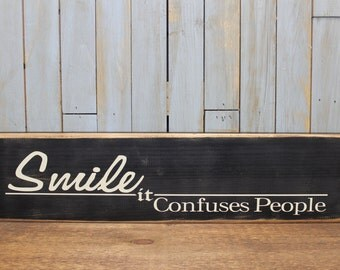 "Wooden Sign ""Smile it confuses people"""