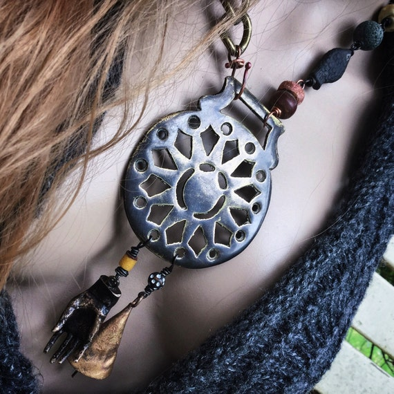Tribal assemblage necklace with large brass focal and cast brass hand