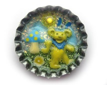 Grateful Dead hat pin, handmade and one of a kind, yellow enamelled dancing bear in bottlecap with mushroom, butterfly and flower, lacquered