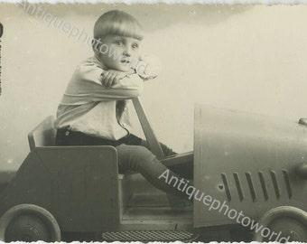 Cute boy in amazing toy car antique photo