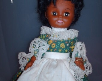 Vintage Gambina  Black Doll with green print dress and pinafore