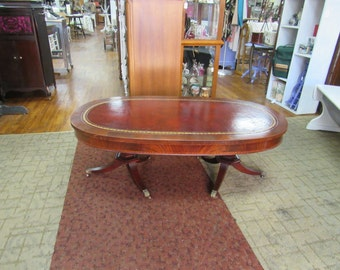 Flame mahogany coffee table oval shaped leather top