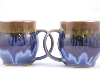 pair of handmade mugs. large pottery mugs. flowing deep blue glaze. handmade in ithaca. under the tree.
