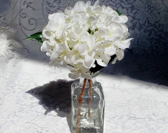 Creamy White Hydrangea Bloom with Green Leaves Arranged in a Square Bottle and Permanently Set with Clear Acrylic Water