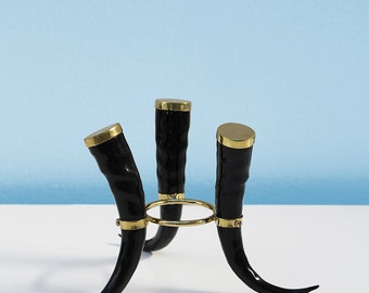 A classic imitation springbok horn stand: Three glossy imitation springbok horns banded together with bronze-type fittings