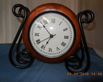 wooden clock with wrought iron stand.