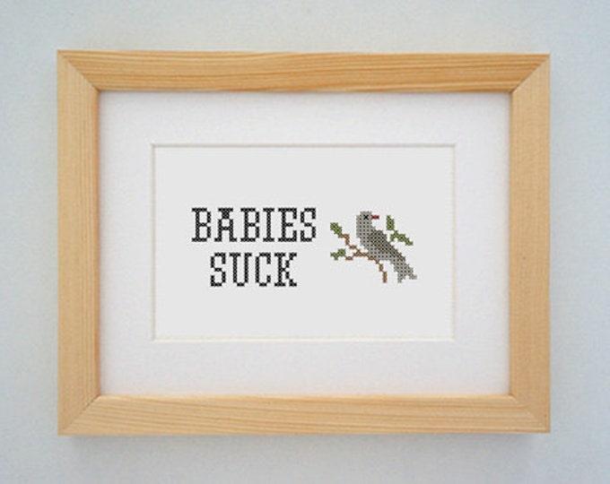 Framed 'Babies suck' cross stitch