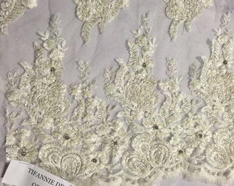 Ivory flowers embroider and heavy beaded on a mesh lace fabric-sold by the yard-