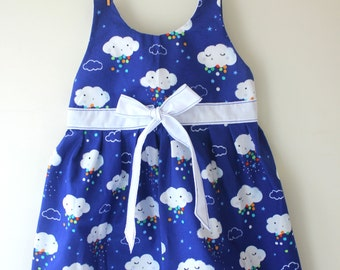 Cloud dress, a beautiful print of white clouds with faces and rainbow raindrops on blue with a white sash with blue contrast stitching