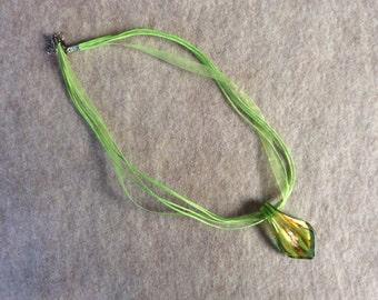 Glass pendant on lime green ribbon cord