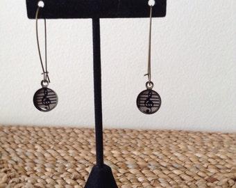 Kidney shaped, music note drop earrings.