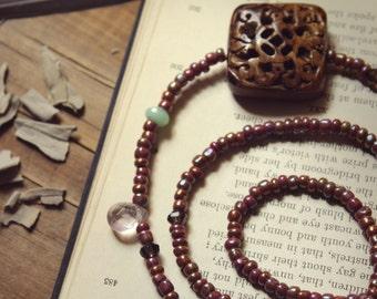 Wildflower. Hand Strung Beaded Necklace. Carved Rosewood, Chyrsoprase, Smoky Quartz, Flourite and Aurora Borealis Mauve Glass.
