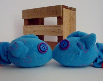 Kissing Sock Fish Made from a Blue Sock with Purple Rings Scattered About and a Red Rim on Each Back Fin With Blue and Purple Button Eyes