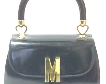 Vintage MOSCHINO black patent enamel Kelly style handbag with M logo and heart motifs.  Masterpiece by Red Wall