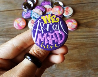 Alice in Wonderland Pin. Hand lettered quote: we are all mad here