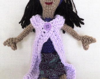 Hand Knitted Doll Wearing a Purple Dress and Jacket