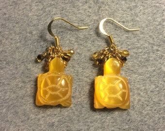 Carved amber fiber optic cats eye turtle bead earrings adorned with tiny dangling amber Czech glass beads.