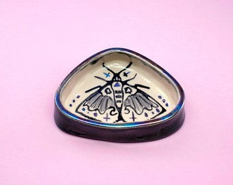 Triangle shaped ceramic ringdish with a moth illustration and rainbowquartz luster details