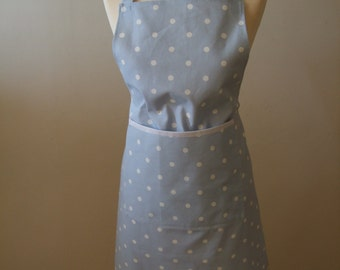 A modern adult apron in organic cotton in a blue dotty design with front patch pocket trimmed in white.