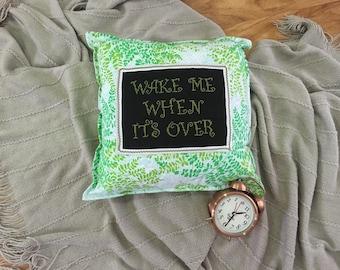 "Sleepyhead's ""Wake me when it's over"" cross-stitch cushion cover."