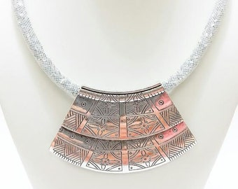 Handmade nylon tubular net statement necklace with crystals, decorated metallic center and magnetic closure.