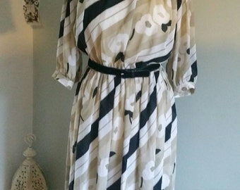 1980s taupe, black and white patterned dress with 3/4 length sleeves and shoulder pads.