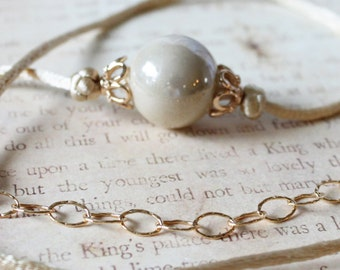 Beige porcelain bead and gold filled knotted cord necklace
