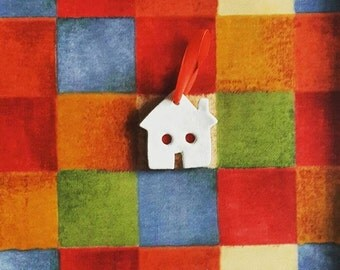 White clay little house with felt curtains