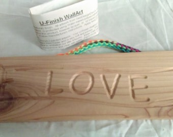 "U-Finish WallArt.  Unfinished cedar ""Love"" wall hanging with knitted multi-colored yarn hanger."