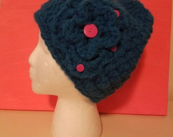 Bright blue beanie hat with flower and pink buttons