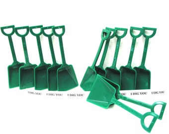 "12 Small Kelly Green Plastic Toy Shovels and 12 ""I Dig You"" Stickers."