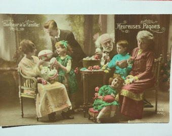 Happy Family reunion * Grandpa, Grandma, parents and children receiving Easter eggs * Colorized photograph on postcard RPPC