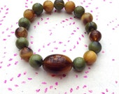 Green, yellow and brown glass beaded elasticated bracelet