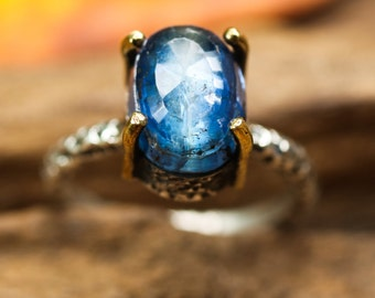 Oxidized sterling silver band ring with blue kyanite oval faceted gemstone in silver bezel and brass prongs setting