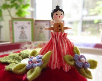 PINELOPE - A Pinny Wooden Doll Pin Topper with Two Itty Bitty Blossoms - Dressed in Red and White Stipes