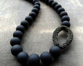 Jet black rubber beads with a golden sparkle for this necklace