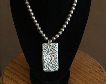 Hand carved porcelain pendant