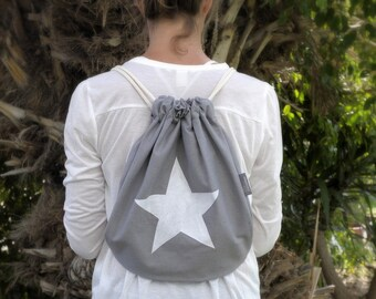 grey drawstring backpack with white star. gym bag. day bag. canvas bag