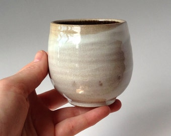 Wheel thrown ceramic cup in soft beige creamy white tones
