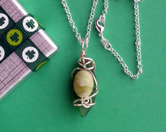 Oval shaped Sea Glass on a Sterling Silver chain with Connemara Marble bead wrapped with non-tarnish wire.