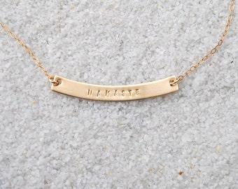 Curved golden bar namaste necklace