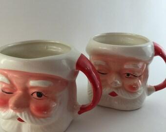 Two vintage ceramic winking Santa mugs