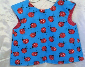 Lady Bug toddler art smock, bib or apron blue lined with a big button in the back making it adjustable from size 2-5 years