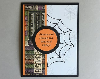 Halloween card with spider webs and colorful books.