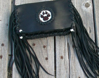 Black leather clutch with fringe and a wolf paw totem