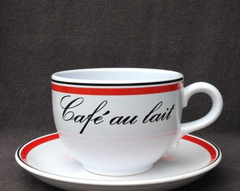 Vintage French Café au lait in a giant cup. Retro breakfast milk and coffee dish souvenir from France.