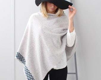 Knitted lambswool grey poncho with blue and cream chevron pattern detail. Perfect gift for Christmas.