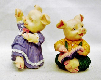 Two Very Cute Well-Defined and Happy Ceramic Pig Figurines-One is dancing for your pleasure, the other is reading a book- Collectibles.