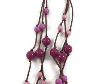 Dark with snap closure Brown multi-string necklace and pink, pale mauve and purple balls